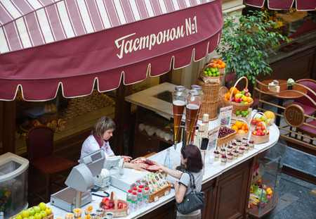 soft drinks: MOSCOW - JULY 29: The seller of fruits, juices and soft drinks allowing delivery to the buyer in the GUM store on July 29, 2014 in Moscow.