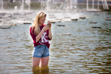 gorky: Mosca -July 31: Beautiful girl standing in water on a background of a fountain in the Gorky Park on July 31, 2014 in Moscow. Editorial