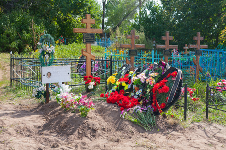 BESTUZHEVO, RUSSIA - AUGUST 26: Graves, flowers, wreaths and crosses in the cemetery on August 26, 2014 in Bestuzhevo village.