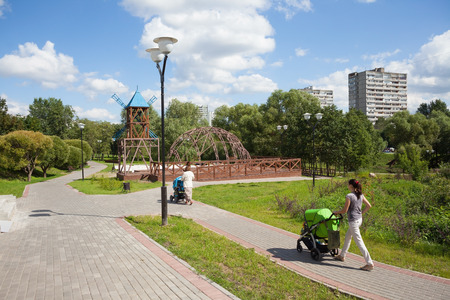 prams: MOSCOW - AUGUST 2: Two women walking with prams in Heritage Village Park in Bibirevo district on August 2, 2014 in Moscow. Bibirevo is administrative district of North-Eastern part of Moscow, Russia.