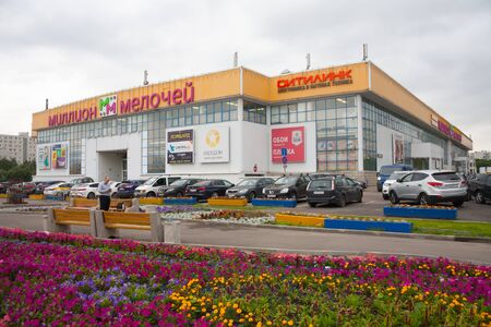 MOSCOW, RUSSIA - JULY 24, 2018: Million Melochey shopping mall building, car parking, benches, flower bed and man in Prishvina street. This street is located in Bibirevo district of Moscow.