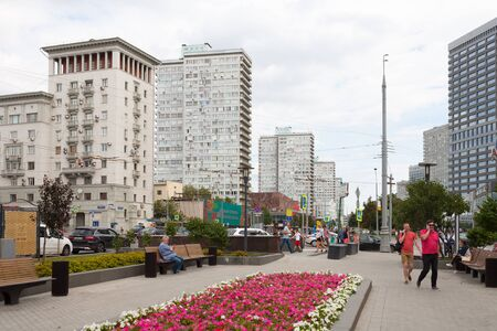 MOSCOW, RUSSIA - AUGUST 20, 2018: People walking near flower bed in Novy Arbat street. This street is located in the center of Moscow. Redactioneel