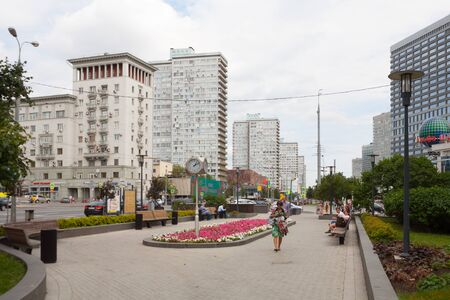 MOSCOW, RUSSIA - AUGUST 20, 2018: People resting near flower bed in Novy Arbat street. This street is located in the center of Moscow.