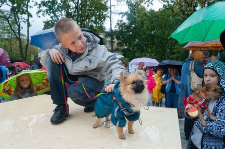 MOSCOW, RUSSIA - SEPTEMBER 16, 2018: Children playing with small dogs in Krasnogvardeiskie Ponds park on autumn rainy day.