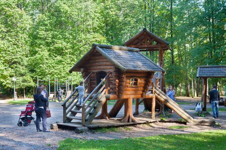 MOSCOW - SEPTEMBER 20, 2018: Adult people, children, wooden houses and trees in childrens playground in Losiny Ostrov (Elk Island) National Park on sunny autumn day. Losiny Ostrov is first national park of Russia.