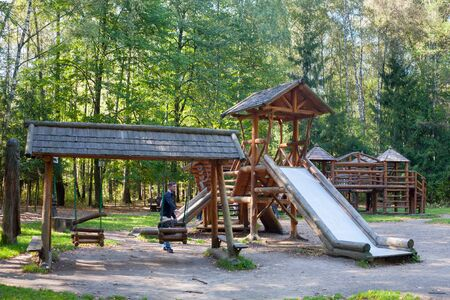 MOSCOW - SEPTEMBER 20, 2018: People, wooden swing, slide and trees in a playground in Losiny Ostrov (Elk Island) National Park on sunny autumn day. Losiny Ostrov is first national park of Russia. Editöryel