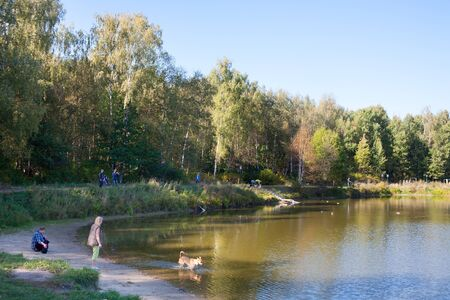MOSCOW - SEPTEMBER 20, 2018: People, dogs, pond and trees in Losiny Ostrov (Elk Island) National Park on sunny autumn day. Losiny Ostrov is first national park of Russia.