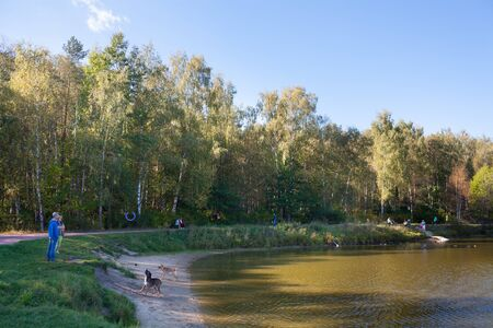 MOSCOW, RUSSIA - SEPTEMBER 20, 2018: People, dogs, trees and pond in Losiny Ostrov (Elk Island) National Park on sunny autumn day. Losiny Ostrov is first national park of Russia.