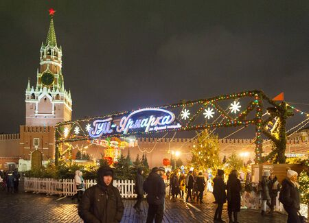 MOSCOW, RUSSIA - DECEMBER 12, 2018: New Year Christmas fair, illumination, people and Moscow Kremlin Spasskaya Tower in Red Square on winter night. Editöryel