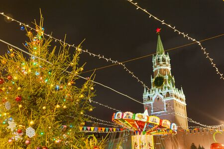 MOSCOW, RUSSIA - DECEMBER 12, 2018: New Years Christmas tree, illumination, and Moscow Kremlin Spasskaya Tower in Red Square on winter night.