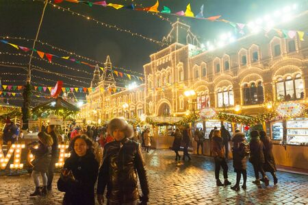 MOSCOW, RUSSIA - DECEMBER 12, 2018: New Year Christmas Fair, people, illumination and GUM building in Red Square on winter night.