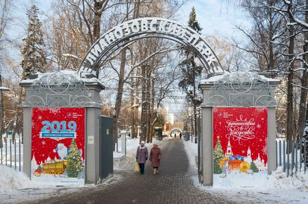 MOSCOW, RUSSIA - JANUARY 09, 2019: Entrance gate to Lianozovo park and two women in Cherepovetskaya street on sunny winter day. Cherepovetskaya street is located in North of Moscow.