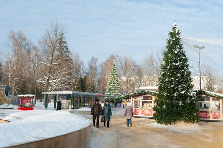 MOSCOW, RUSSIA - JANUARY 09, 2019: People strolling near Christmas trees and food pavilions in Lianozovo park in Cherepovetskaya street on sunny winter day. Cherepovetskaya street is located in North of Moscow. Editöryel