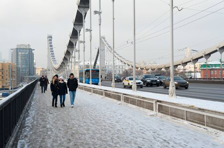 MOSCOW, RUSSIA - JANUARY 10, 2019: People walking along Krymsky Bridge on winter day. Krymsky or Crimean Bridge is steel suspension bridge over Moskva River.