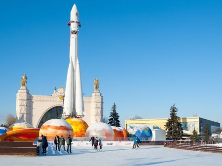 MOSCOW, RUSSIA - JANUARY 22, 2019: People and ice rink against rocket at VDNKh on a winter sunny day. VDNKh is permanent general purpose trade show and amusement park. Editöryel