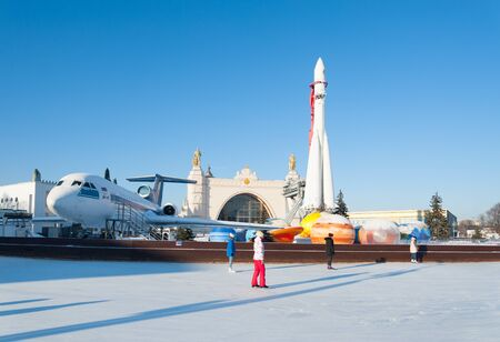 MOSCOW, RUSSIA - JANUARY 22, 2019: People and ice  rink against rocket and plane at VDNKh on winter sunny day. VDNKh is permanent general purpose trade show and amusement park.