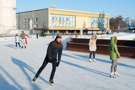 MOSCOW, RUSSIA - JANUARY 22, 2019: People skating on ice rink in VDNKh on winter sunny day. VDNKh is permanent general purpose trade show and amusement park.