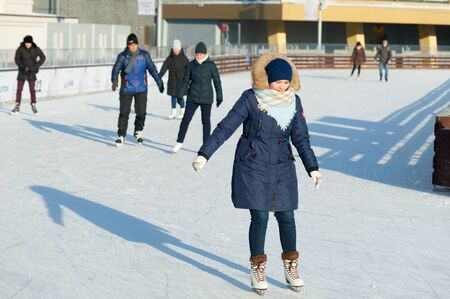 MOSCOW, RUSSIA - JANUARY 22, 2019: Young woman in blue and people skating in VDNKh on winter sunny day. VDNKh is permanent general purpose trade show and amusement park. Editöryel