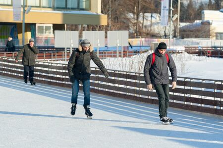 MOSCOW, RUSSIA - JANUARY 22, 2019: Two young guys and senior man skating in VDNKh on winter sunny day. VDNKh is permanent general purpose trade show and amusement park.