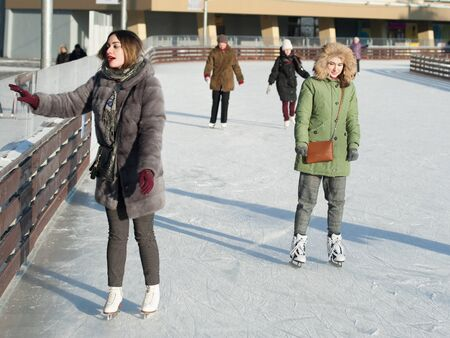 MOSCOW, RUSSIA - JANUARY 22, 2019: Two beautiful girls and people skating in VDNKh on winter sunny day. VDNKh is permanent general purpose trade show and amusement park.
