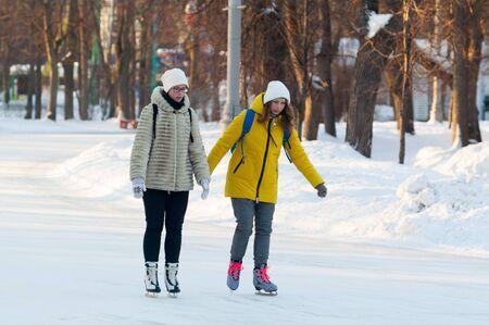 MOSCOW, RUSSIA - JANUARY 23, 2019: Two beautiful young girls skating in Sokolniki Park on winter sunny day. Sokolniki Park is not far from center of city, near Sokolnicheskaya Gate.
