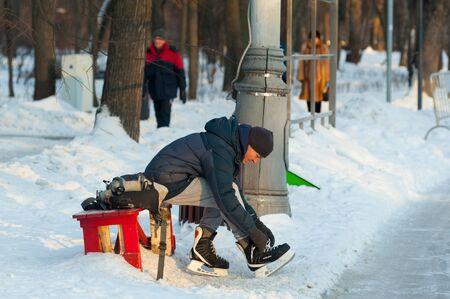 MOSCOW, RUSSIA - JANUARY 23, 2019: Adult man putting on skates in Sokolniki Park on winter sunny day. Sokolniki Park is not far from center of city, near Sokolnicheskaya Gate.