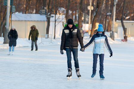 MOSCOW, RUSSIA - JANUARY 23, 2019: Young man and woman skating in Sokolniki Park on winter sunny day. Sokolniki Park is not far from center of city, near Sokolnicheskaya Gate.
