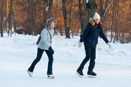 MOSCOW, RUSSIA - JANUARY 23, 2019: Two happy women smiling and skating in Sokolniki Park on winter sunny day. Sokolniki Park is not far from center of city, near Sokolnicheskaya Gate.