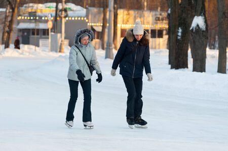 MOSCOW, RUSSIA - JANUARY 23, 2019: Two women skating in Sokolniki Park on winter sunny day. Sokolniki Park is not far from center of city, near Sokolnicheskaya Gate.