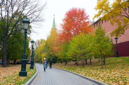 Moscow, Russia - October 14, 2019: Alley in Alexander Garden and Moscow Kremlin in autumn. Alexander Garden and Kremlin are located in center of Moscow.