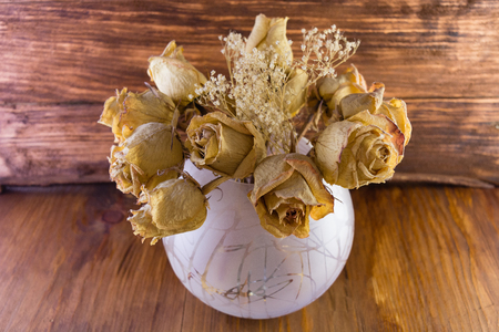 a jar stand: the macro dried-up old dusty roses in a jug on a wooden background