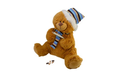 glass thermometer: isolate the macro childrens toy teddy bear in a scarf with tablets takes temperature a mercury glass thermometer