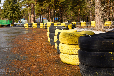 Fragment of a barrier on a carting track made of an old painted tires Фото со стока