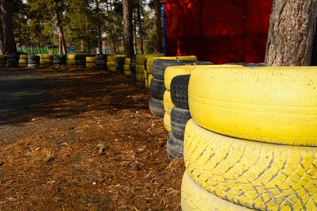 carting: Fragment of a barrier on a carting track made of an old painted tires Stock Photo