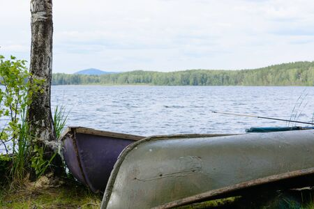 the boat lies on the bank of the lake. summer Russia South Ural. wooden boat.