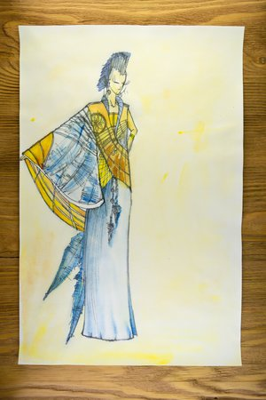 the drawing of designer clothes pencils on paper. background wooden table.