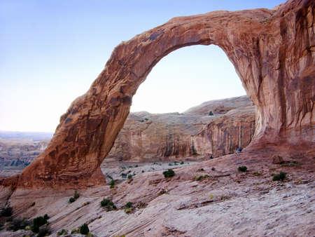 dwarfs: Massive Corona Arch dwarfs hikers; Moab, Utah