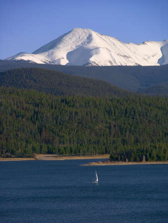 A lone sailboat ventures out while the snow-covered Rockies provide a backdrop