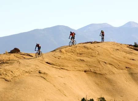 Mountain bikers climb rugged slickrock in Moab, Utah