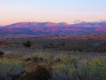 The final moments of daylight turn the LaSalle Mountains purple; Moab, Utah Stock Photo