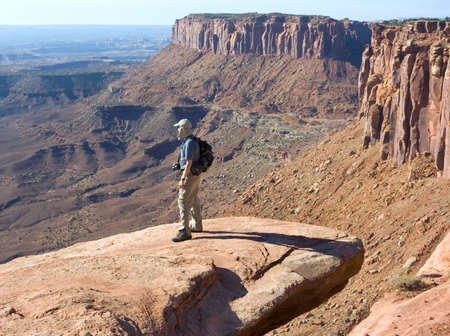 Climber finds a high perch from which to take a photo; Canyonlands, Utah Reklamní fotografie