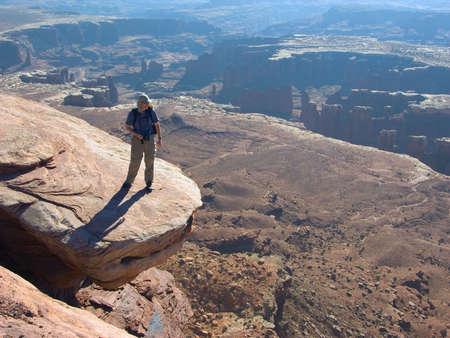 Hiker admires vista from a risky perch