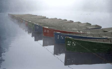 Colorful rowboats lie at rest just after sunrise. Reklamní fotografie