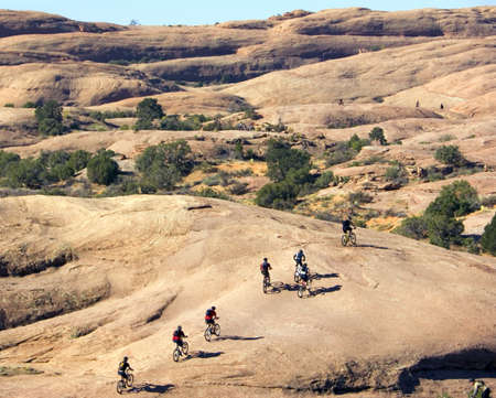 Multiple bike groups tackle the sheer rock in Moab, Utah