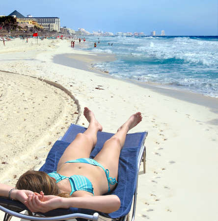 Woman relaxes in the morning sun on a Cancun beach