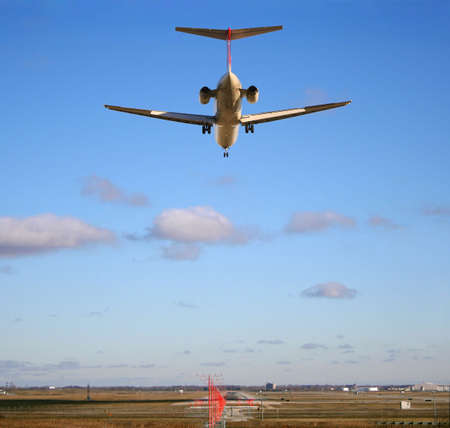 Runway stretches out ahead of jet just about to land photo