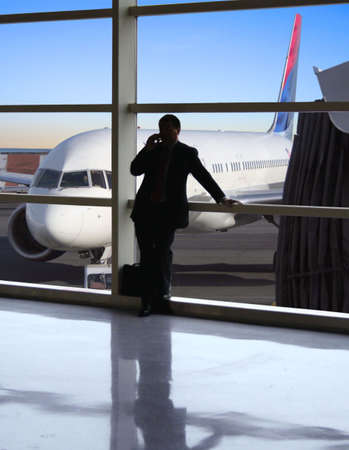 Business traveler makes a call while waiting for his flight photo