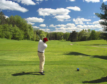 Golfer tees off with a long drive