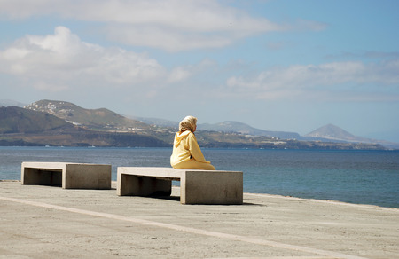 illegal immigrant: Immigrant woman sitting and looking at the sea in Spain