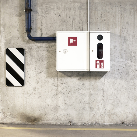 hosepipe: A fire extinguisher and a fire-hose in the white box on concrete wall